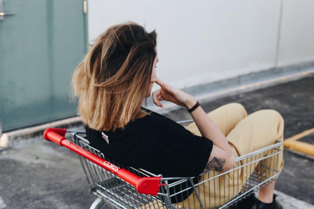 mloda dziewczyna siedzi w wozku zakupowym
